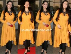 Actress Charmi Kaur in yellow high - low hem salwar paired up with black leggings. Charmy Kaur, Designer Dresses, Designer Kurtis, South India, India Fashion, Anarkali, Indian Beauty, Black Leggings, Frocks