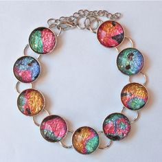 "Bright fun colors of pink, green, and blue with a touch of sunshine shimmer in this silver-plated  link bracelet, featuring tiny abstracts from the original PiCassieO print ""Midsummer 3"", from the Midsummer Doldrums series (see my earrings for the story!).  Glass domes are 14 mm diameter.  Fits  ..."