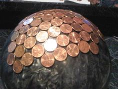 House of Hawthornes: Bowling Ball Yard Art- use 1/4 cup white vinegar and 1 teaspoon of table salt to clean pennies. Next use DAP Clear Silicone Rubber Sealant for Doors and Windows to glue the pennies onto the bowling ball.