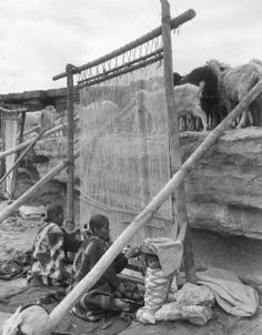 Navajo women weave a rug with sheep and goats above.