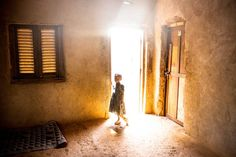 A young girls stands in the doorway of a house, two days after a member of her family was killed by a grenade said to be launched by a member of Séléka. Bangui, Central African Republic. Nov. 14, 2013.