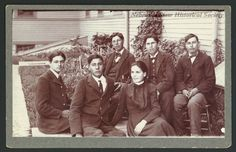 This shows a group photo of High School students at the Santee Normal Training School. The shot consists of five boys and a girl, dressed in uniforms of the school, posing for the camera. They are all seated and a school building is seen in the background. A sidewalk is on the far left of the photo. Date	circa 1900