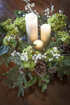 Centerpiece: 3 white candles varying heights, pine tree branches, white berry branches, pine cones, green hydrangea