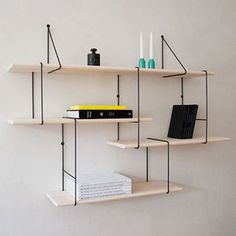 """Described as an update of the """"classic string shelf"""", this customisable shelving system by Berlin design firm Studio Hausen comprises a series of steel and ash wood modules."""