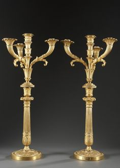 A pair of gilt bronze candelabra with four removable sconces. Each candlestick rests on a round base decorated with a frieze of circumscribed foliage on a matte ground. The partially...