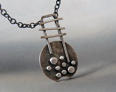 This lovely pendant is entirely handmade in sterling silver. The granules have been formed individually, hammered then soldered to the piece. The pendant has been oxidized to bring out the detail and then polished. The pendant hangs on a sterling silver chain ( 45 cm / 18 ) . Length of the pendant: approximately 2.6 cm ( 1.4). Width : approximately 1.6 cm ( 0.6) at the widest point. The pendant is sent in a gift box. Each piece is hand made , so slight variations may exist from the item…