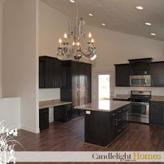 Modern dark cabinets in traditional kitchen with chandelier and vaulted ceiling. At Candlelight Homes, we build beautiful