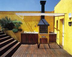 A estrutura de ferro com pintura eletrostática sustenta a cobertura de vidro laminado, que aumenta a área de trabalho na churrasqueira pré-fabricada. Projeto do arquiteto Gilberto Belleza.