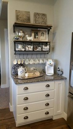 Coffee bar. White Keurig. Hobby Lobby shelf with hooks and baskets. Electric kettle with cozy. Tea chest. French press.