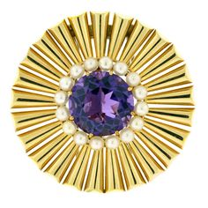 The Tiffany & Co. sunburst design brooch, centers upon a circular-cut amethyst weighing approximately 15 carats, approximately 18 mm in diameter, within a conforming border of round cultured pearls...