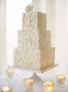 Ivory, three tier, square wedding cake with floral indentation and flower topper.