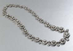 A Victorian cluster necklace, mounted in silver-upon-gold, set with approximately 27.00ct of old-cut diamonds. This adaptable necklace has clasps which allow it to break into three pieces. We believe that the necklace was made circa 1880 to 1890.
