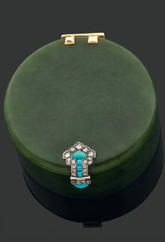 AN ART DECO BOX BY CARTIER. Composed of nephrite jade, with gold hinge, Persian style clasp embellished with turquoise and rose cut diamonds. Mounted in platinum and white gold. French.