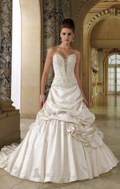 Draped Skirt Dress by David Tutera   Item #112202W by David Tutera (Fall, 2012)        $1,303.00  Turn heads in this stunning satin bridal gown by David Tutera 112202W! The ornately beaded sweetheart bodice features an attached hand-beaded illusion modesty piece. The dropped waist and full lace-up corset back add to the romantic style. The most stunning feature of the floor length gown is the side draped pick up skirt with chapel length train and subtle bubble hem. Measured from hollow to…