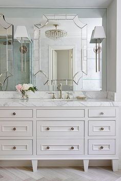 Exquisite bathroom boasts a white footed custom washstand adorned with nickel knobs topped with ...
