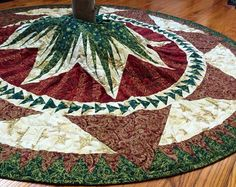 Looking for that perfect finishing touch for the center of your Christmas celebration? This elaborate Christmas tree skirt will add just the right level of luxe while showcasing your tree.  The attention to detail in this tree skirt is just stunning: there are 240 pieces in the ring of green flying geese (triangles) alone. The total tree skirt has just shy of eight hundred pieces, each hand cut from premium 100% quilting cotton fabric, metallic etched to catch and shimmer in the lights on…