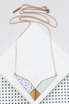 Long necklace with a V shaped dominant pendant comprised of FORMICA® and brass plated in high quality 24K gold or silver, according to your choice.