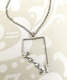 """Polished Stainless Steel Chain length: 18"""" Custom Design: Home Means Nevada Pendant is small and delicate. Width is about .75"""" and Height is a little under 1"""""""