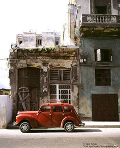 Cuba Island, Capital city Havana Old town american retro car is parked in front of gone to rack and ruin buildings