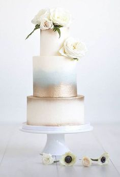 Pale Blue and Gold Three-Tiered Wedding Cake. Washes of pale blue and metallic gold elevate this classic wedding cake.