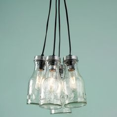 """Got milk? What's more fun for your kitchen, pantry, or workspace lighting than a cluster of milk bottles! This vintage throwback pendant light has a modern industrial feel with the addition of decorative tubular light bulbs. The quart size bottles of textured clear glass with brushed pewter lids allow plenty of light with farm fresh country appeal. The bottle cluster is 9""""Hx12""""W hanging from 17"""" of black pendant cords through a bronze lid size disc with adjustable chain to... SHADES OF LIGHT"""