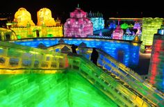 The colorful lights of the ice block sculptures create a intriguing overall scene for tourists. Harbin Ice Festival.