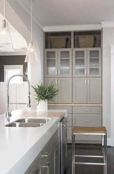 greige cabinets, silver handles, white counters