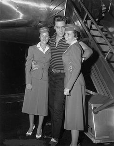 Elvis Presley poses for a portrait with two stewardesses after disembarking from a plane on August 16 1956 in Los Angeles...