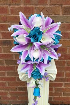 "Dimension: DIA 10"" x 20"" Long Classic Cascade silk floweråÊarrangement. Made of open roses in shades of turquoise, purple,and white. Tiger lily and real touch calla lilies. åÊ"