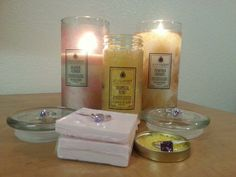 Two candles and a jar of aroma beads with their rings.