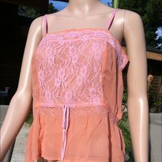 """Peach lacy babydoll tank. 100% silk. 100% silk peach tank. Adjustable straps and adjustable tie waist. Side measures 14"""". Across bust 17"""". Top of strap to bottom 21"""". Size 8 but also would fit size 6. Somwhat sheer. plenty Tops Tank Tops"""