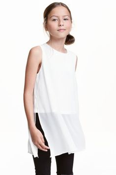 Sleeveless chiffon blouse: Sleeveless blouse in airy chiffon with a wrapover back with a button at the back of the neck and high slits in the sides. Jersey lining.