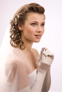 A little vintage romance goes a long way and this partial updo is different and glamorous. bridal updo bride The bang area is twisted up and over and it is pulled back and worked into the side swept ponytail which is full of gentle curls. Tiny white beads are worked into the style. A veil is attached to the back of this asymmetrical do. This would be perfect for the woman looking to add some 1940s charm to her wedding day. More on Vintage Bridal Updo
