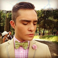 Chuck Bass from Gossip Girl wearing a pink gingham shirt, beige blazer, and bow tie in an outdoor setting