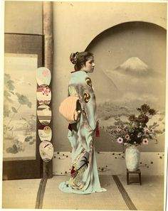 Geisha showing her obi at a highly decorated room