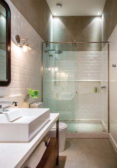 Seguindo o clima urbano do restante do apê, o banheiro recebeu azulejos no estilo do metrô londrino e, no alto da parede, acabamento no tom de concreto (Ekko).