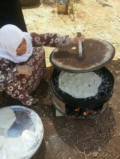 Palestinian beautiful bread   baking her bread the traditional way.  over heated rocks.  (they are clean!)