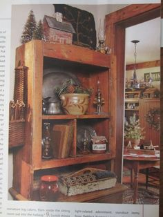 January 2011, p.49 ~ LOOK at this wonderful cabinet display!!!  I LOVE the mish-mash of items on here -- pewter, a wooden carrier that I WANT, the fabric covered books the basket on the side, and, OH! - look at all those different OIL LAMPS!!  LOVE them!