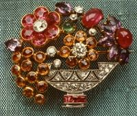 A platinum and gold brooch with diamonds, rubies, sapphires, topazes, amethysts and an emerald in the shape of a basket of flowers. Art Deco, circa 1925.