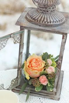 This decoration is great - the vintage lantern is almost melancholy but when paired with the bright flowers, is suddenly made bright. ~A