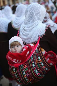 A child hangs in a traditional woolen sack from the back of its grandmother on the main square during a traditional wedding celebration in Ribnovo, Bulgaria on January 2014 [Credit : Sean Gallup/Getty Images] Mother And Child Reunion, Mother And Father, Mother And Baby, Kids Around The World, We Are The World, People Of The World, Precious Children, Beautiful Children, Happy Baby