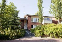 Rinteeseen rakennettua taloa ympäröivät vehmaat puut, pensaat sekä ruusu- ja villiviiniköynnökset.