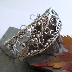 Lace - Filigree Inspired cuff - Silver  Inspired by beautifully ornate filigree designs, I developed this cuff from my Filigree inspired ring design. Swirling wire is contrasted with intricately woven leaves and extra detail has been added with silver beads of graduating sizes, which has all been perfectly balanced with the open spaces.