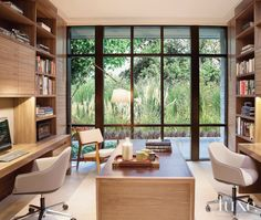 A shared office space features a pair of Vitra Softshell chairs and a custom leather-wrapped walnut-and-steel desk by interior designer Mimi Shin.