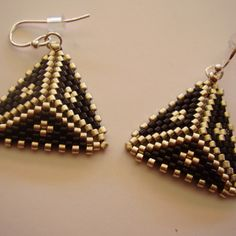 Puffy triangle shape earrings in a color pallet of black and silver beads are stitched in a puffy triangle shape. The earrings measure 1.50 inches long from the top of the French silver-filled ear wires to the bottom of the earring. All earrings include a rubber clutch for the ear wires so you never lose another earring.  You will find this and many other earring styles in the Earrings and Seasonal section of my shop.  Gift box is included at no extra charge. Item #EA202
