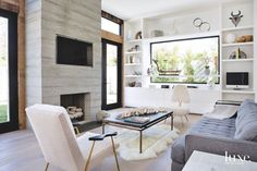 Steel-and-glass doors by Euroline Steel Windows & Doors fold open to the rear terrace and large courtyard. A board-form concrete fireplace—constructed by the project's builders, Matthew Pierce and Stephen Stone—anchors the terrace. The teak sofa, armchairs, coffee table and pendant are by RH.