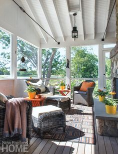 A sunny screened-in porch is cooled by Cape Cod breezes and scattered with comfy chairs atop a Stark area rug. Photography: Nat Rea