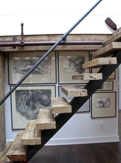 Rustic industrial/modern floating stairs with metal piping used as a handrail and detailing for split levels.
