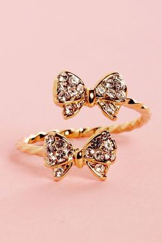 Give yourself the gift of dazzling digits with the Bowfinger Gold Rhinestone Bow Ring! A twisted metal band opens up in front to show off two pretty, rhinestone-covered bows. Bows measure just under Cute Jewelry, Jewelry Box, Jewelry Accessories, Fashion Accessories, Jewlery, Jewelry Rings, Resin Jewelry, Women Accessories, Unique Jewelry