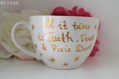 DIY Tassen bemalen, hier mit goldenem Schriftzug: All it takes is Faith, Trust & Pixie Dust. Pixie, Trust, Take That, Faith, Mugs, Tableware, Diy, Stained Glass, Dinnerware
